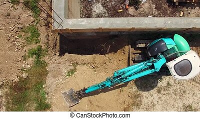 A small blue excavator works near the building. bird's eye...
