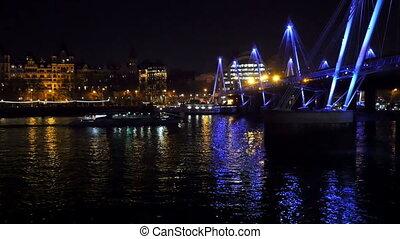 A small boat crossing under the bridge in London