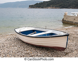 A small boat in the harbor of Valun on a cloudy day in spring