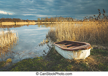 A small boat on the shore of a lake