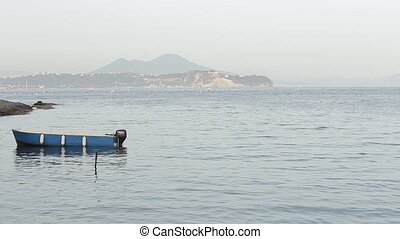 a small boat sailing along the sea, on the background of an island with mountains