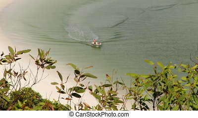 A small boat sailing in the shoreline - A shot of a beach...