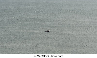 A small boat with a fisherman in the middle of a huge ocean