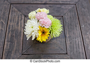 a small bouquet of colorful flowers on a well used old desk or w