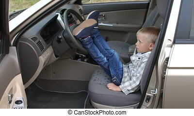 A small boy in a car, he threw his feet on the steering wheel.