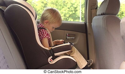 A small boy of five years is sitting in a car seat in a car and playing a tablet