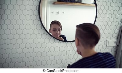 A small boy washing face in the bathroom in the morning,...