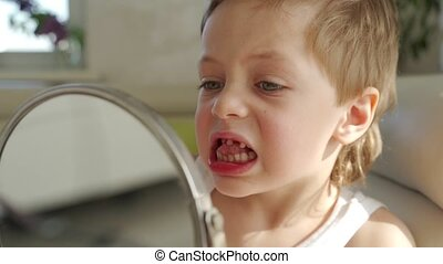 a small boy with blond hair with mirror opening his mouth to...