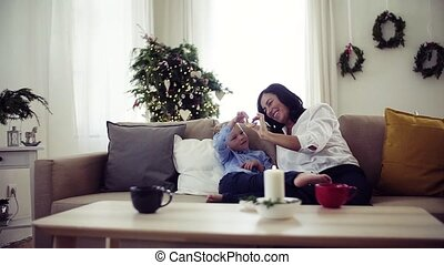 A small boy with grandmother sitting on a sofa at home at...