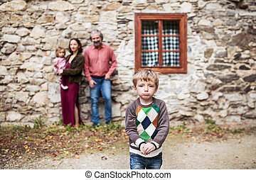 A small boy with his family standing in front of old stone house.