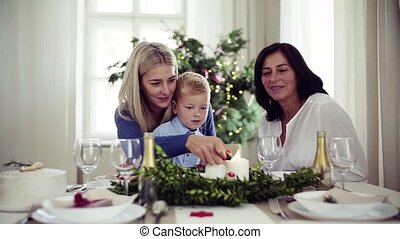 A small boy with mother and grandmother at home at Christmas time, lighting candles.