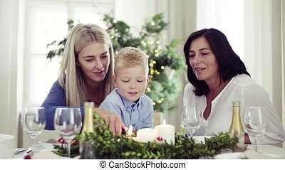 A small boy with mother and grandmother at home at Christmas...