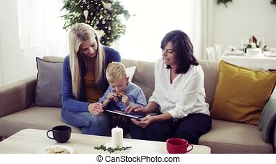 A small boy with mother and grandmother at home at Christmas time, using tablet.