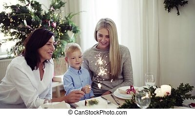 A small boy with mother and grandmother holding sparkles at Christmas time.