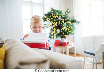A small boy with opening up a present at home at Christmas time.