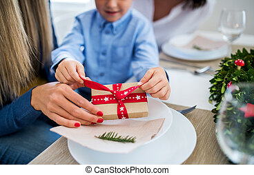 A small boy with present and mother sitting at a table at home at Christmas time.