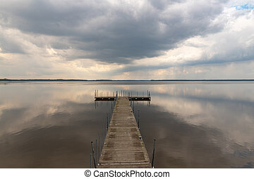 A small bridge over the lake. Reflection of clouds on the lake's surface.