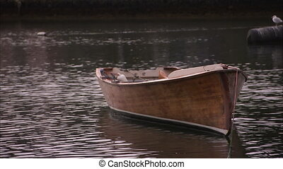 A small brown boat on a canal - A zoomed in shot of a brown...