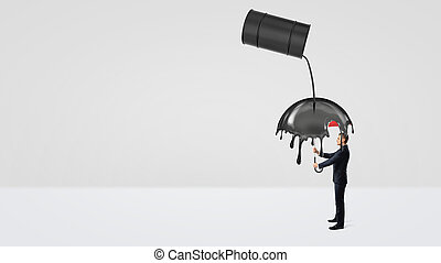 A small businessman hiding under an umbrella from crude oil leaking of a large black barrel.