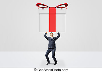 A small businessman holding a giant gift box with both hands above his head.