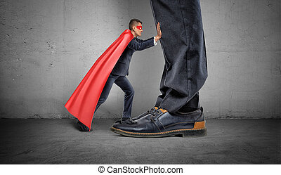 A small businessman in a superhero cape trying to push away giant man legs.