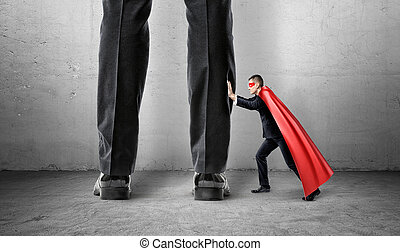 A small businessman in a superman cape trying to push away giant man legs.