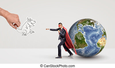 A small businessman in superhero cape beside a globe ready to fight off a paper dragon held by a giant hand.
