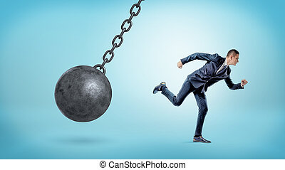 A small businessman running away from a giant black wrecking ball on a chain.