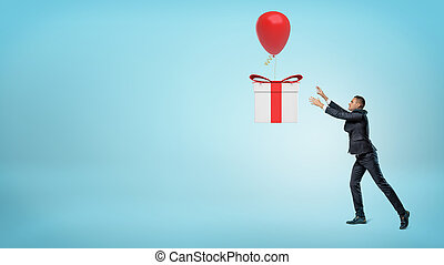 A small businessman trying to catch a big gift box that is flying away on a balloon.