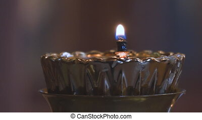 A small candle in a Church candlestick in the Orthodox...