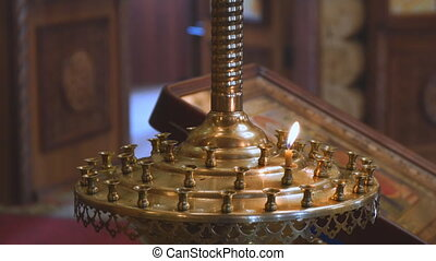 A small candle in a Church candlestick in the Orthodox Church