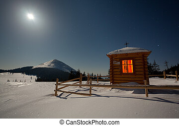A small chapel in the mountains at the winter. Night with moon and stars