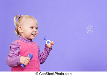 A small charming Caucasian poppet plays with bubbles on a violet background