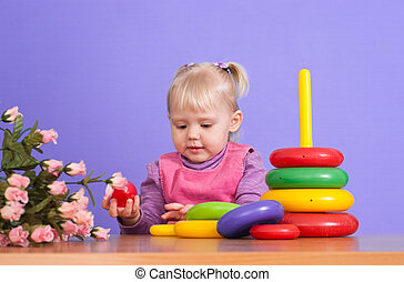 A small charming Caucasian poppet plays with toy on a violet background