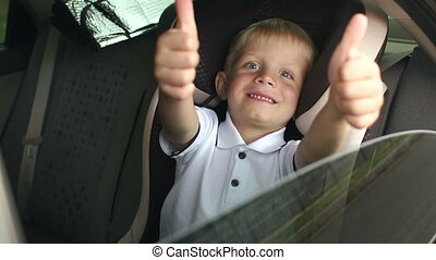 A small cheerful boy sits in a brown child car seat and shows his thumb up.