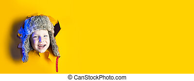 a small cheerful child in a winter hat with earflaps smiles from a hole in yellow cardboard background