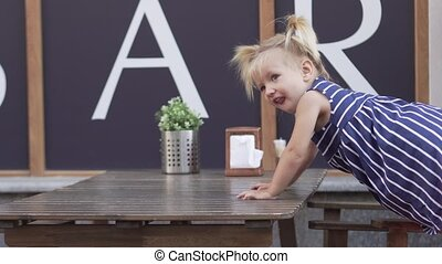 A small cheerful girl is sitting at a table in a cafe