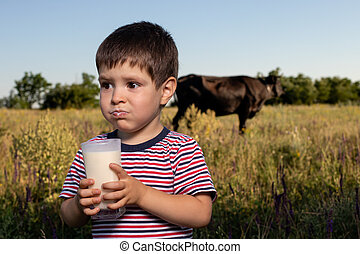 A small child boy 3 years old for the first time tastes cow's milk, does not like milk, crooked, writhes the face.