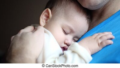 a small child fell asleep in his father's arms. dad rocking the baby to sleep. close-up . 4k.