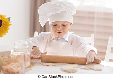 A small child in the form of a cook rolls the dough on a table
