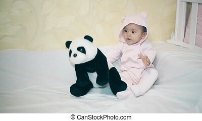A small child is lying next to a Panda on a white blanket