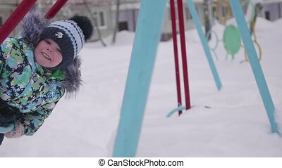 A small child is playing in winter Park. A child on a swing. A Sunny winter day. Fun and games in the fresh air.