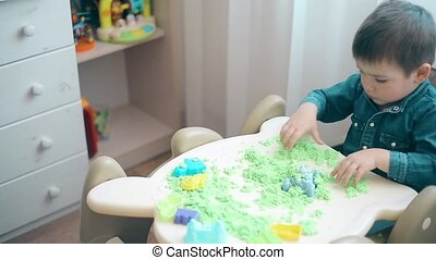 A small child is playing with kinetic sand and develops motor skills of hands