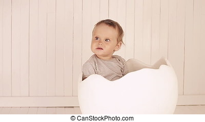 A small child is sitting in a toy egg shell.