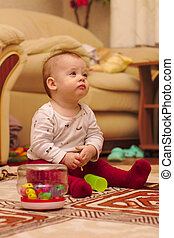 a small child is sitting on the floor in the room and playing with ear sticks