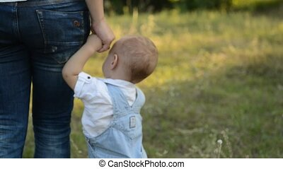 a small child is standing next to his mother