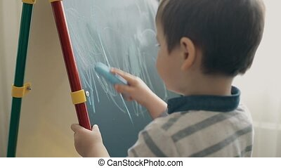 A small child learns to draw with chalk on a blackboard
