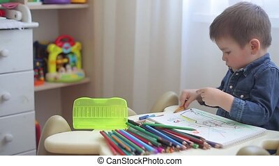 A small child learns to draw with colored pencils on paper