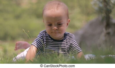 A small child lies on the grass cry close-up
