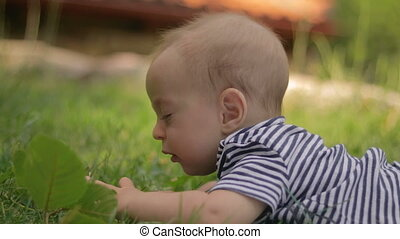 A small child lies on the grass crying close-up